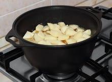Potatissnitt i tärning som låter småkoka i den svarta metallkastrullen på gas-ugnen Arkivfoton