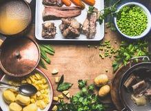 Potatissoppa med den gröna ärtan och kött som lagar mat förberedelsen på det lantliga köksbordet, bästa sikt Royaltyfri Foto