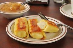 Potato blintzes and applesauce. Golden potato blintzes with applesauce and coffee Stock Photo