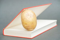 Potato in a book Stock Images