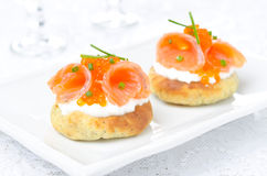 Potato bun with salted salmon, red caviar and chives, horizontal. Potato bun with salted salmon, red caviar and chives on the plate, horizontal closeup Royalty Free Stock Images