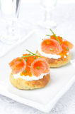 Potato bun with salted salmon, red caviar and chives, vertical. Potato bun with salted salmon, red caviar and chives on the white plate, vertical Royalty Free Stock Photo