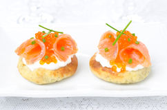 Potato bun with salted salmon, red caviar and green onion. On white plate, horizontal close-up Stock Photo