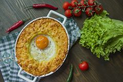 Potato casserole with bolognese. Baked potato casserole with egg and grated cheese in a ceramic oval baking sheet. Wooden dark stock photography