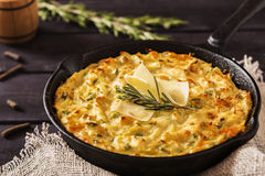 Potato Casserole with cheese. Potato casserole in the cheese in a cast iron frying pan with a sprig of rosemary and slices of cheese on dark wooden background Royalty Free Stock Photography