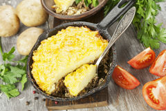 Potato casserole with meat. On the wooden table Royalty Free Stock Images