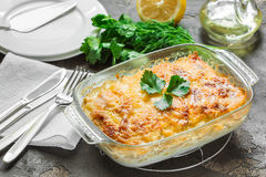 Potato casserole with melted cheese, fresh green apple and lemon. Potato gratin with cream cheese and fresh herbs Royalty Free Stock Photos