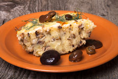 Potato casserole with salted mushrooms in a clay plate on old wo Stock Images