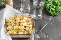 Potato casserole with vegetables and herbs, spicy spices, a glas Stock Photography