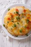 Potato casserole on a white plate closeup. Vertical top view Stock Photography