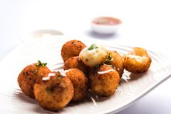 Potato cheese balls or croquettes or aloo tikki. Fried potato cheese balls or croquettes with tomato ketchup. Selective focus royalty free stock photography