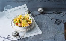 Potato cheese salad with vegetables and viennese sausages in a bowl on a table with christmas decoration. Cheese is sliced in star. Shape royalty free stock image