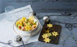 Potato cheese salad with vegetables and viennese sausages in a bowl on a table with christmas decoration. Cheese is sliced in star. Shape stock photos