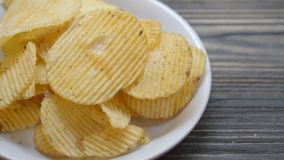 Potato chip fried crisp on dish on the wood table, snack food appetizer with delicious and tasty but unhealthy. Moving motion stock footage
