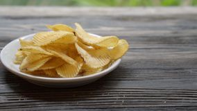 Potato chip fried crisp on dish on the wood table, snack food appetizer with delicious and tasty but unhealthy. Moving motion stock video footage