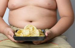 Potato chip in obese fat boy hand Royalty Free Stock Image