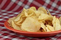 Potato Chips. Golden salted potato chips on orange plate Stock Photo