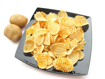 Potato Chips. Handmade potato chips and whole potatoes isolated on white background Stock Images