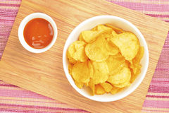 Potato chips. Fried potatoes on the wood plate Royalty Free Stock Images