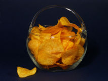 Potato chips. Bowl of potato chips over black background stock photos