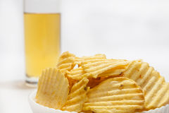 Potato chips with beer in the glass Royalty Free Stock Images