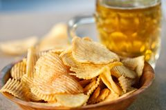 Potato chips and beer on a wooden table royalty free stock photo