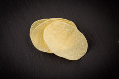Potato chips on a black background Stock Images
