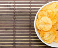 Potato chips in bowl on bamboo mat Stock Image