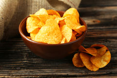 Potato chips in bowl on brown wooden background. Royalty Free Stock Images