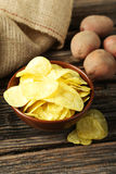Potato chips in bowl on the brown wooden background Royalty Free Stock Photos