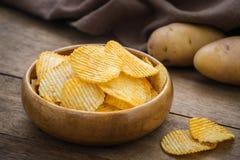 Potato chips in bowl and fresh potato Royalty Free Stock Photo