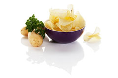 Potato chips in bowl with potatoes Stock Photography