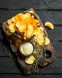 Potato chips in bowl with sauce and thyme. On black rustic background stock image