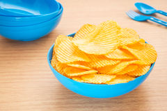 Potato chips in bowl on table Royalty Free Stock Images
