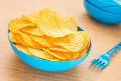 Potato chips in bowl on table Royalty Free Stock Photos