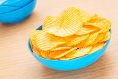 Potato chips in bowl on table Royalty Free Stock Image