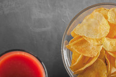 Potato chips in bowl with a tomato juice in glass Stock Images