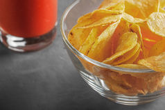 Potato chips in bowl with a tomato juice in glass Stock Image