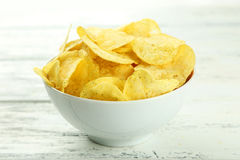 Potato chips in bowl on white wooden background Stock Photo