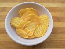Potato chips in bowl on wooden background Royalty Free Stock Images