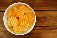 Potato chips in bowl on a wooden background, top view Royalty Free Stock Photo
