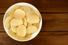 Potato chips in bowl on a wooden background, top view Royalty Free Stock Images