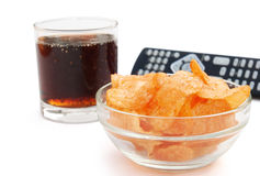 Potato chips and cola and remote control Stock Photo