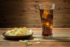 Potato chips with cola on a wooden background stock photo