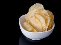 Potato chips, crisps in bowl on black shiny surface Stock Images