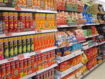 Potato chips or crisps on a store shelf. A display of potato chips or crisps on shelves in a supermarket. Sometimes called junk food.This supermarket in stock photo