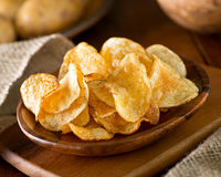 Potato Chips. Delicious home made potato chips with sea salt and black pepper against a rustic background Stock Photos