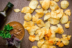 Potato chips with dipping sauce on a wooden table. Unhealthy food on a wooden background. Royalty Free Stock Photography
