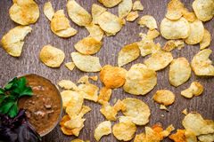Potato chips with dipping sauce on a wooden table. Unhealthy food on a wooden background. Stock Photos