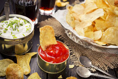 Potato chips with dipping sauces on a rustic table Stock Photography